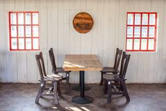 Free Old Wooden Table And Chairs Decorate In Restaurant With Red Window On White Wall In The Background. Stock Images - 115916974
