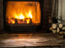 Old Wooden Table And Fireplace With Warm Fire. Stock Photos