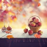 Old wooden table with apples and autumn leaves. Old wooden table with red apples and autumn leaves stock photography