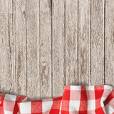Old wooden table background with picnic tablecloth
