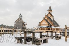 Old wooden table with benches in front of Ancient wooden Slavic church on a snowy landscape. Historical and Architectural Museum i. N the open air. Kiev, Ukraine Stock Image