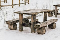 Old wooden table with benches on the snow at the end of winter. Old wooden table and benches on the snow at the end of winter. Spring is coming Stock Photo