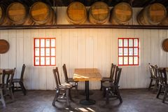 Old wooden table and chairs locate in restaurant with wooden wine barrel interior in restaurant. royalty free stock image