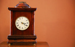 Old wooden table clock. Scene of the old wooden table clock on the table Stock Photo