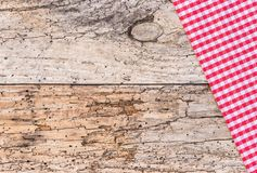 Rustic old wooden table top shot with red checked tablecloth. Old wooden table covered with red tablecloth, top view, copy space Royalty Free Stock Photos