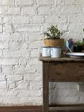 Old wooden table decoration. The back is white brick wall. royalty free stock photo