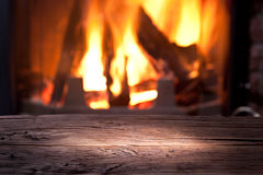 Old wooden table and fireplace. Stock Photo