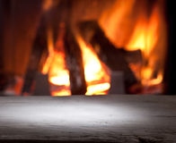 Old wooden table and fireplace. Stock Photos