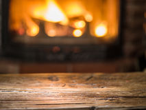 Old wooden table and fireplace with warm fire. Royalty Free Stock Images
