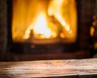 Old wooden table and fireplace with warm fire. Stock Photo