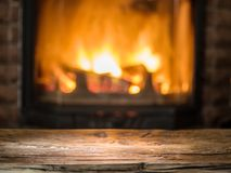 Old wooden table and fireplace with warm fire. Royalty Free Stock Image