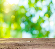 Old wooden table with green foliage. Royalty Free Stock Photos