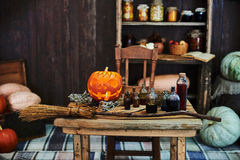 Old wooden table, hallowen pumpkin, dried herbs and bottles, a top view, in the studio, in the afternoon. Old wooden table, orange hallowen pumpkin, dried herbs Stock Image