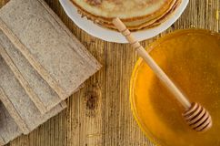 Homemade honey bread pancakes on a windward wooden background. On an old wooden table lie pancakes honey with a spoon for honey and bread Stock Images