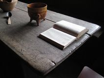 Old wooden table with open book serene light stock photography