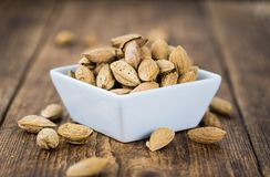 Old wooden table with roasted Almonds in the shell. An old wooden table with roasted Almonds in the shell as detailed close-up shot selective focus Stock Images