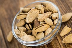 Old wooden table with roasted Almonds in the shell. An old wooden table with roasted Almonds in the shell as detailed close-up shot selective focus Royalty Free Stock Photography