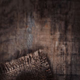 Old wooden  table with sack cloth  in dark interior with copy sp Royalty Free Stock Image