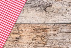 Old wooden table top view, covered with rustic red checked napkin. Red checked table cloth on old rustic wood background with copy space Stock Photos