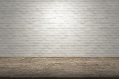 Old wooden table with white bricks wall background. Old brown wooden table with white bricks wall of blur background, copy space royalty free stock photography
