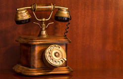 Old Wooden Telephone. An old antique telephone against a wooden background Royalty Free Stock Image