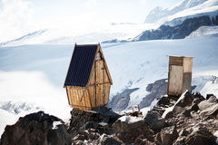Old wooden toilets on permafrost glaciers in mountains Stock Photos