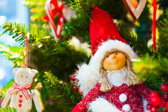 Old wooden toy bear with a red bow ribbon hanging on Christmas Fir Tree Toys  Burning Candles, Boxes, Balls, Pine Cones Stock Image