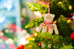 Old wooden toy bear with a red bow ribbon hanging on Christmas tree in the background other decorations and garlands Royalty Free Stock Photo