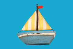 Old wooden toy boat. Isolated on blue stock photo