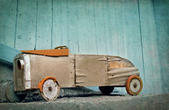 Old wooden toy car. Old wooden rustic toy car on a light blue textured artistic background Royalty Free Stock Photos