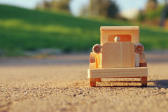 old wooden toy car on the road outdoors in the park at sunset Stock Photos