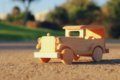 old wooden toy car on the road outdoors in the park at sunset Royalty Free Stock Images