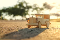Old wooden toy car on the road outdoors in the park at sunset. Nostalgia and simplicity concept Royalty Free Stock Images