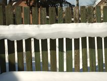 Old wooden village fence covered with snow. Snowy winter in the Stock Photo