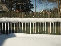Old wooden village fence covered with snow. Snowy winter in the Royalty Free Stock Images