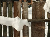 Old wooden village fence covered with snow. Snowy winter in the Royalty Free Stock Image