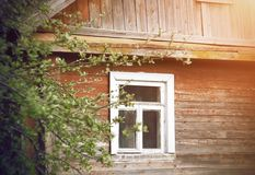 Old wooden village house with a white frame on the window royalty free stock images