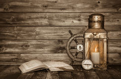 Old wooden vintage background with book, lantern and nautical de. Old wooden vintage background with book, lantern, candle and nautical decoration Royalty Free Stock Images