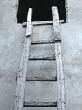 Old wooden vintage cuve ladder near a wall Stock Photos