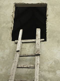 Old wooden vintage cuve ladder near a wall Stock Photo