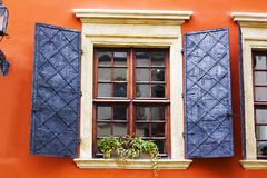 Old wooden vintage square window with open metal shutters. On background of orange wall of house Stock Photos