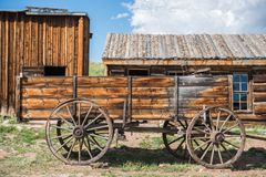 Old Wooden Wagon. And Aged Log Cabins Royalty Free Stock Photography
