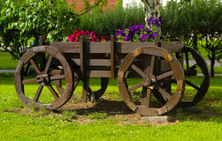 Old wooden wagon with flowers. Rustic decoration. Decorative trolley in retro style. Royalty Free Stock Photos