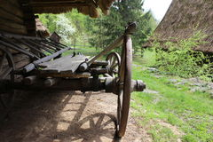 Old wooden wagon near the ancient log house Royalty Free Stock Photos