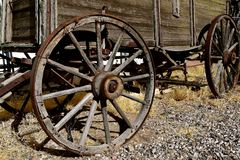 Old wooden wagon with spoke wheels. Hub, rim, and spokes of old wheels supporting a weathered wood wagon Royalty Free Stock Photo