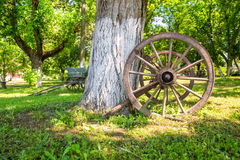 Old wooden wagon wheel. Close-up of an old wooden wagon wheel in the foreground Royalty Free Stock Photography