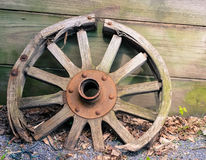 Old wooden wagon wheel leaning against wall Royalty Free Stock Image
