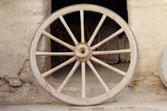 An old wooden wagon wheel leaning up against soil wall Stock Images