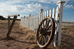 An old wooden wagon wheel leans against a wooden fence. An old wooden wagon wheel leans against a wooden fence in a rural part of New Mexico Stock Photography