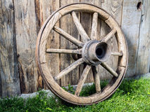Old wooden wagon wheel. Resting against rustic wooden fence Stock Photography